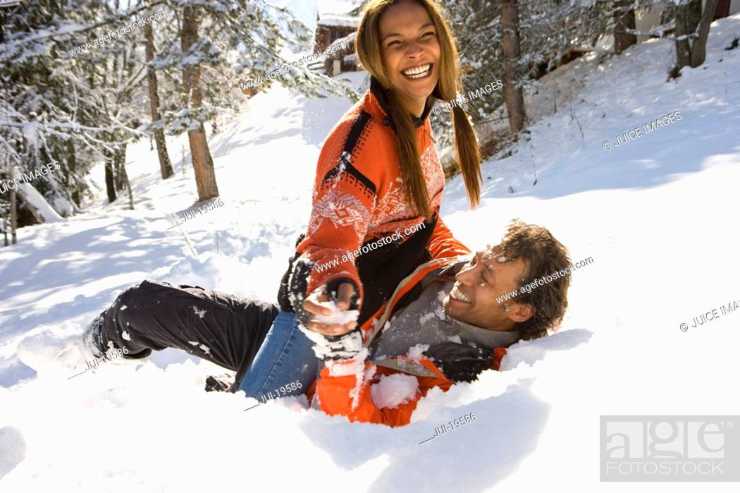 Stock Photo: Mixed race couple playing in snow.