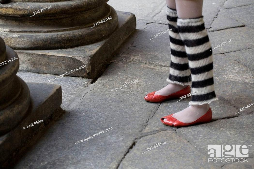 Stock Photo: Girl's legs with red shoes.