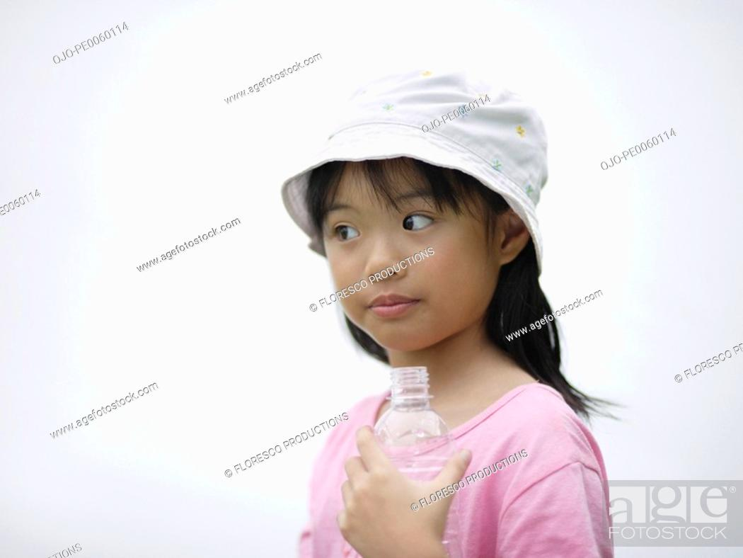 Stock Photo: Young girl indoors holding water bottle.