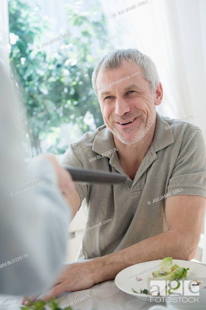 Stock Photo: Older Caucasian man paying bill in restaurant.