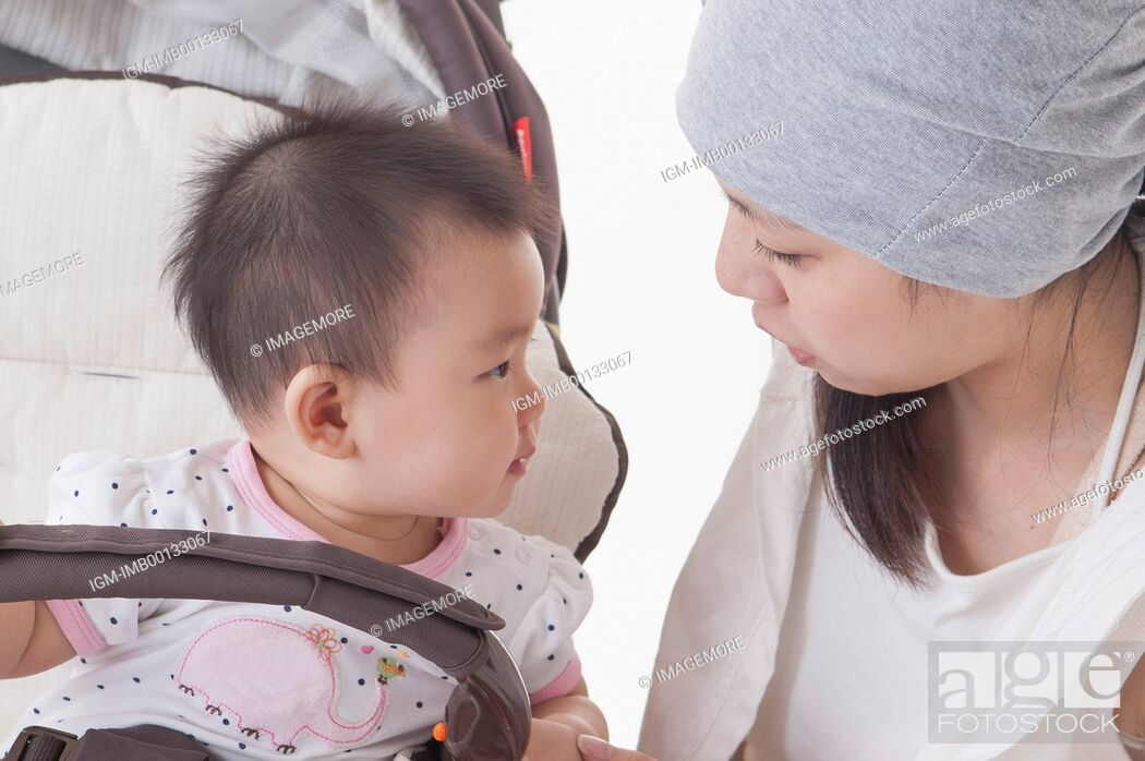 Stock Photo: Mother crouching near the baby carriage and looking at baby girl,.