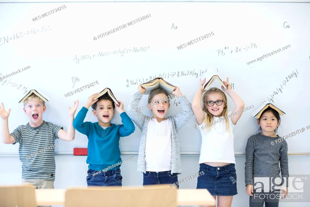 Stock Photo: Happy pupils with books above their heads standing at whiteboard with formulas in class.