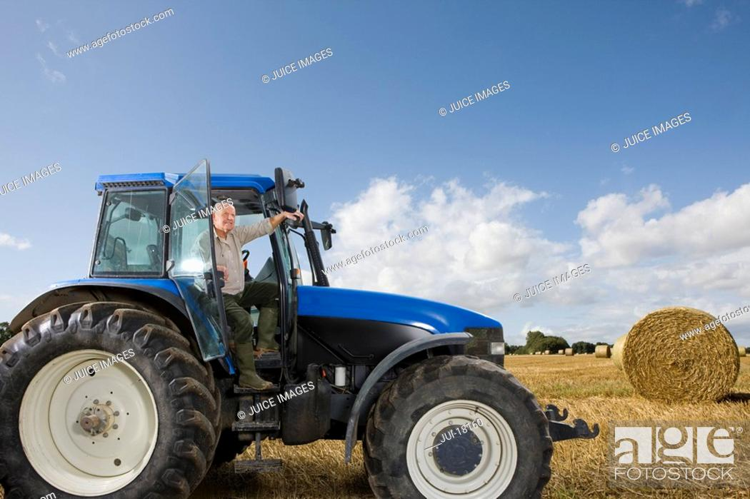Stock Photo: Farmer stepping down from tractor in hay field.