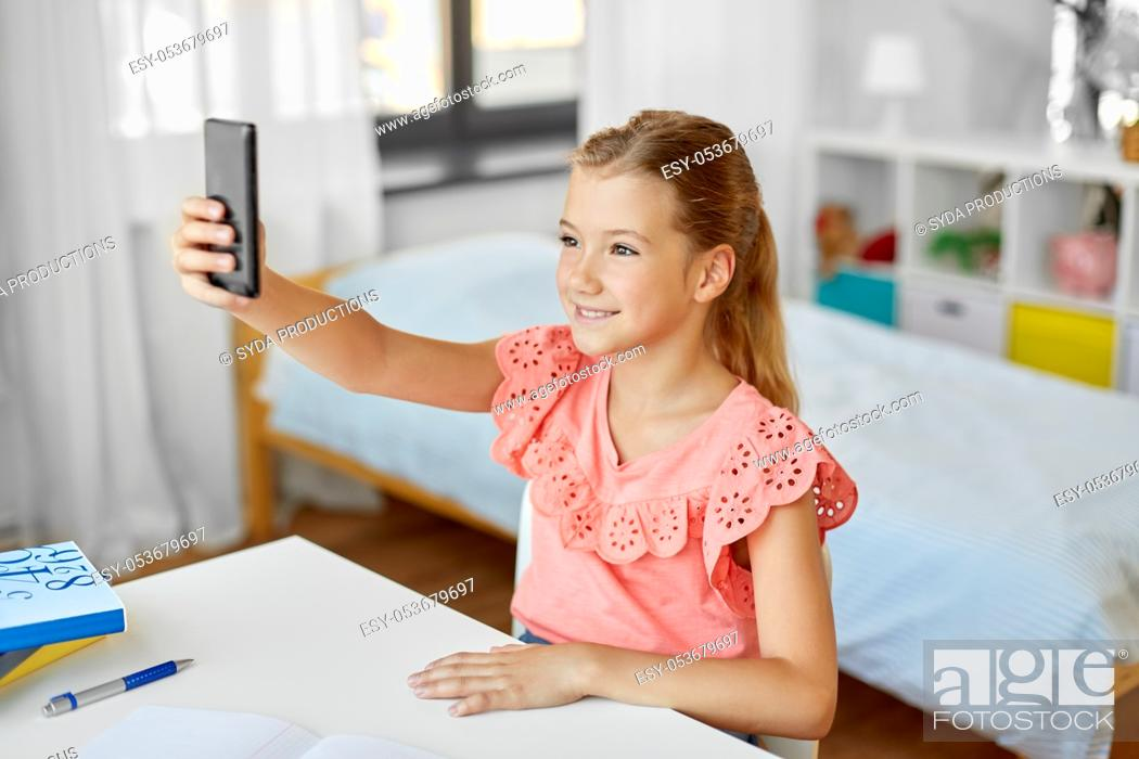 Stock Photo: happy girl with smartphone taking selfie at home.