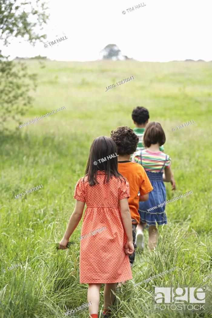Stock Photo: Children 7-9 walking in field.