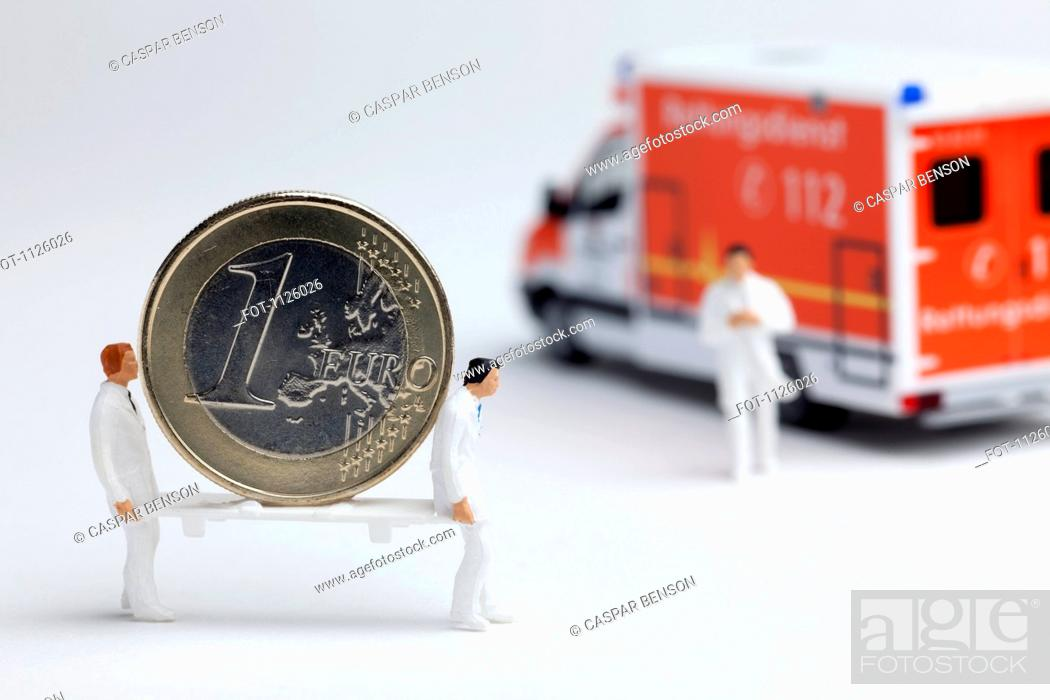 Stock Photo: Miniature paramedic figurines carrying a euro coin on a stretcher to a toy ambulance.