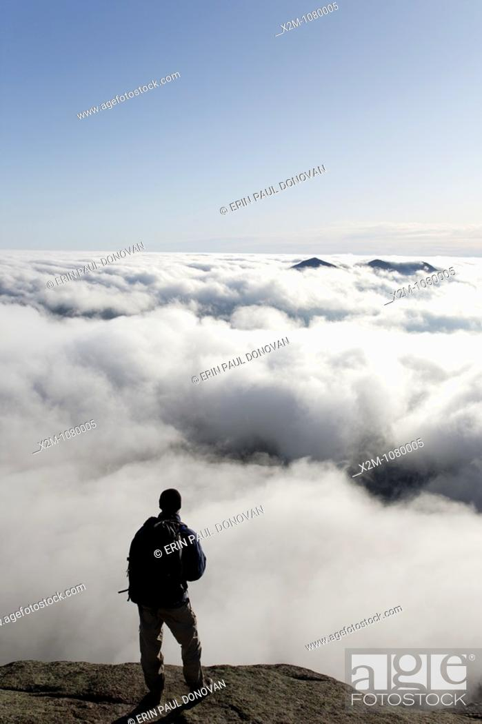 Stock Photo: A hiker takes in the view of undercast from the summit of Mount Osceola in the White Mountains, New Hampshire USA.