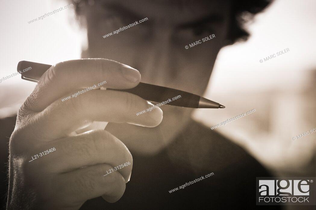 Stock Photo: Man holding ballpoint pen.