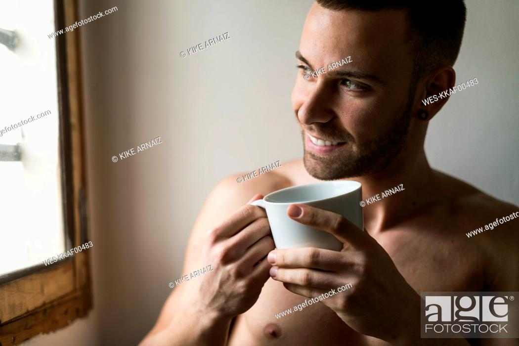 Stock Photo: Attractive young amn with six pack drinking coffee.