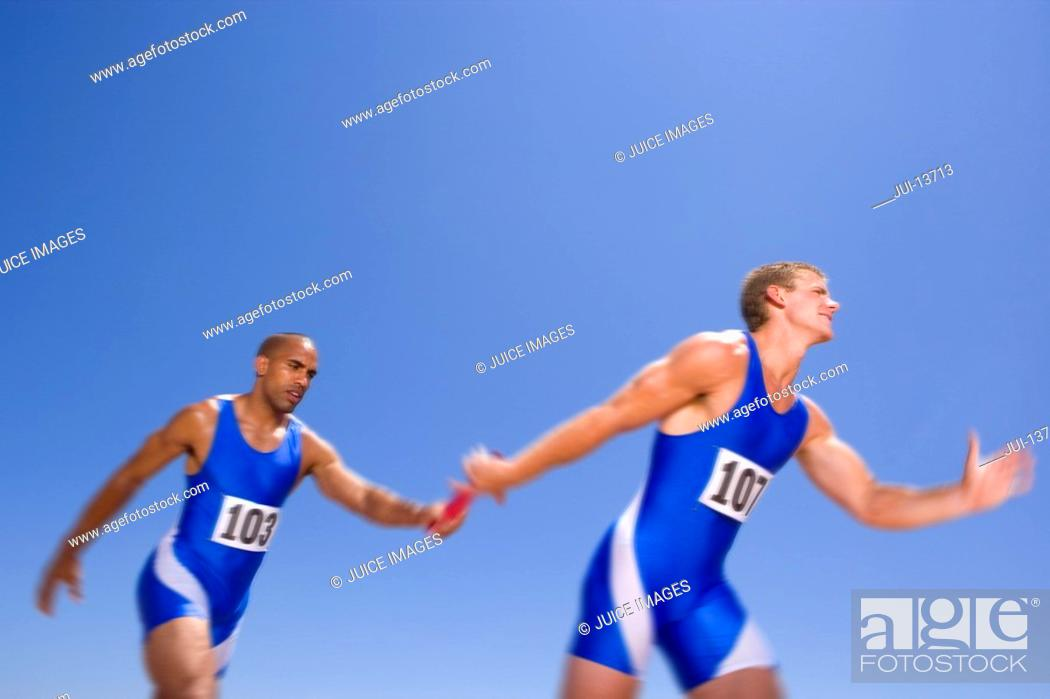Stock Photo: Young male athletes passing relay race baton.