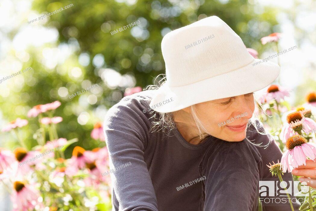 Stock Photo: Caucasian woman examining flowers.