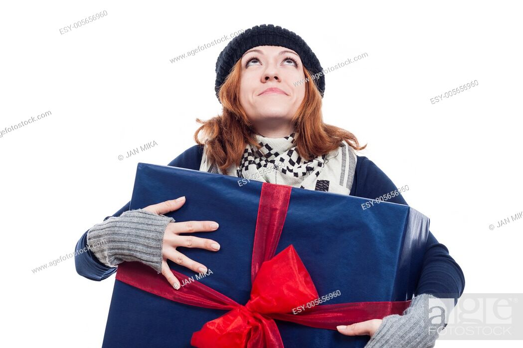Stock Photo: Thankful winter woman holding big present and looking up, isolated on white background.