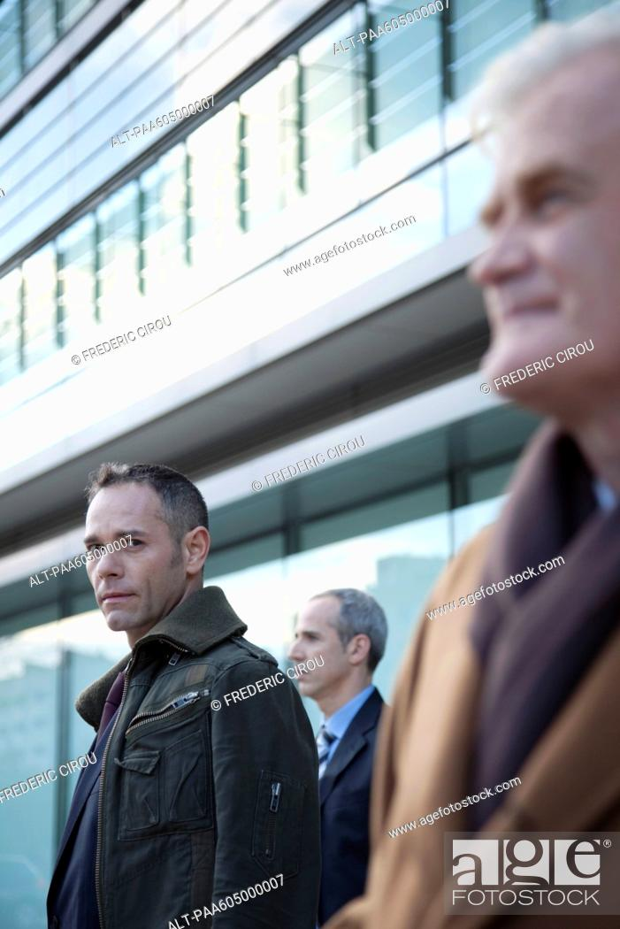 Stock Photo: Businessmen standing in front of building.