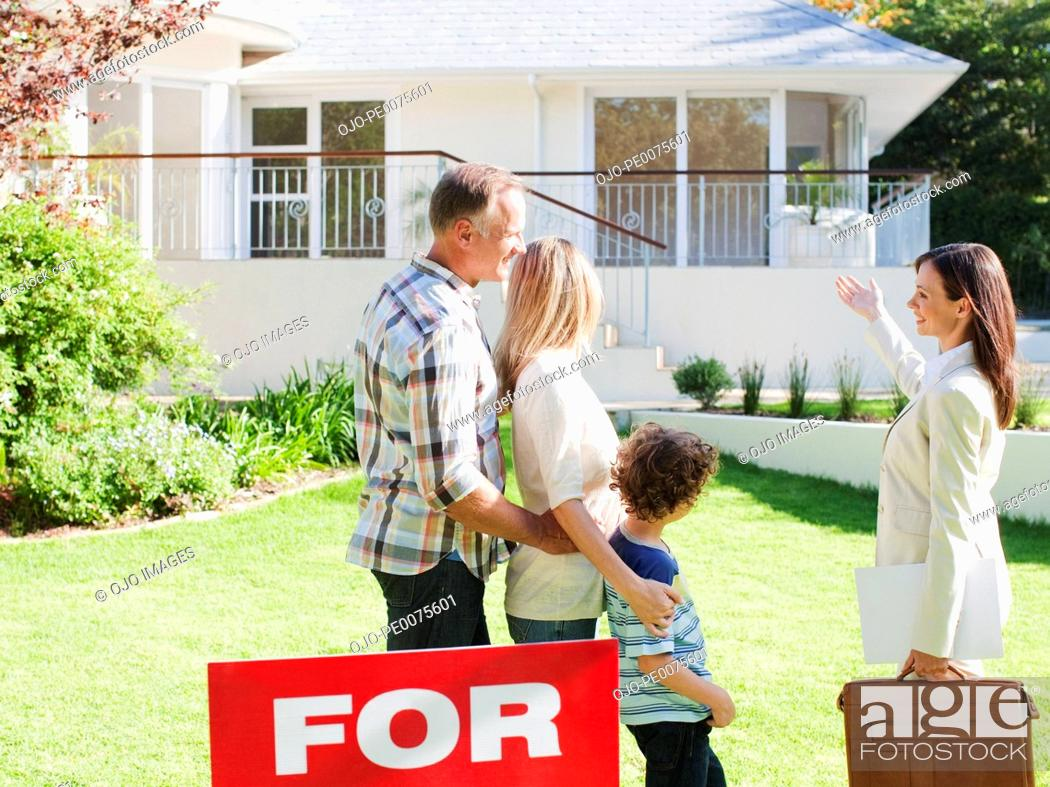 Stock Photo: Realtor showing family a house for sale.