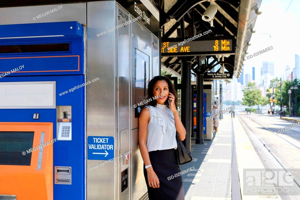 Stock Photo: Businesswoman using cellphone by ticket machine.