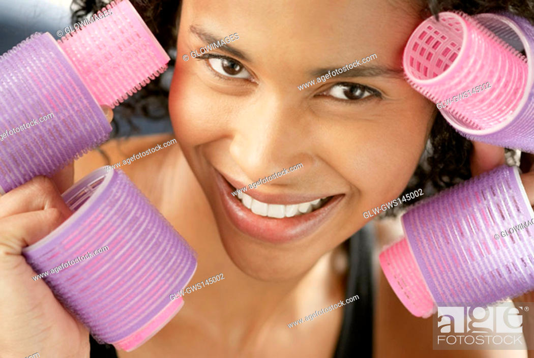 Stock Photo: Portrait of a young woman holding curlers.