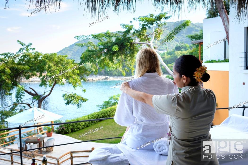 Stock Photo: Massage therapist helping woman to undress at luxury wellness retreat - Mismaloya, Puerto Vallarta South Shore, Jalisco, Mexico.