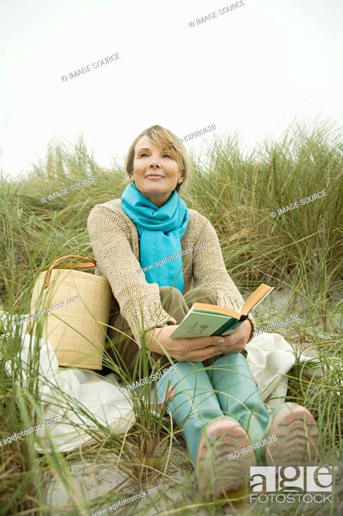 Stock Photo: Woman at the coast with a book.