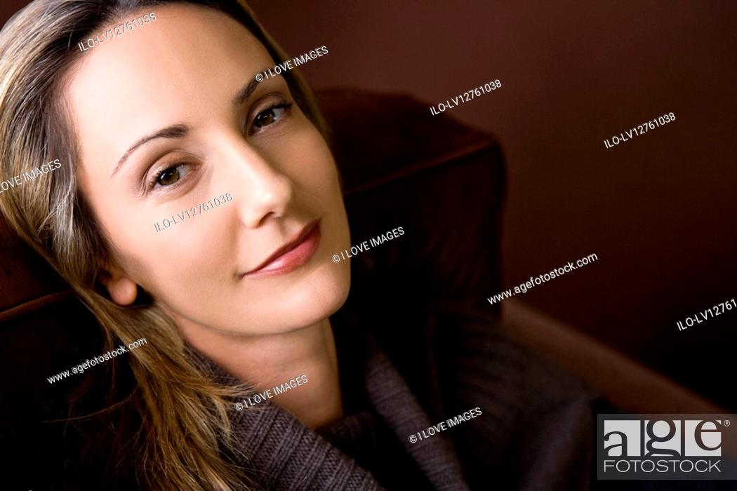 Stock Photo: Portrait of a mid adult woman resting in an armchair.