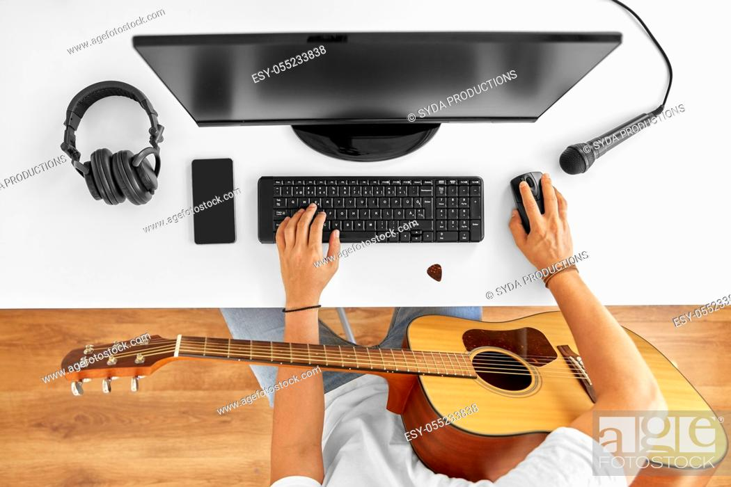Stock Photo: young man with computer and guitar at table.