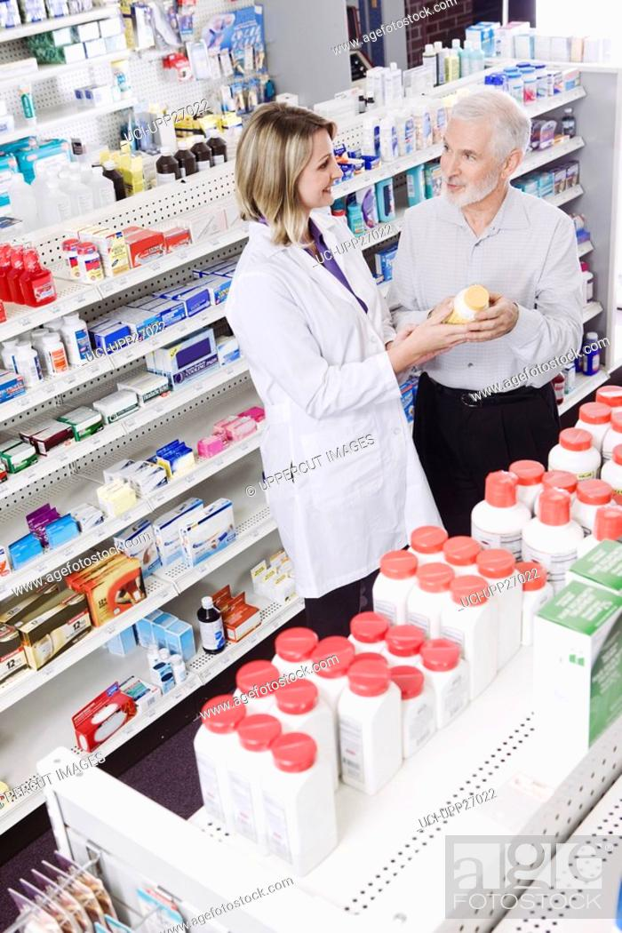 Stock Photo: Pharmacist helping customer with over-the-counter products.