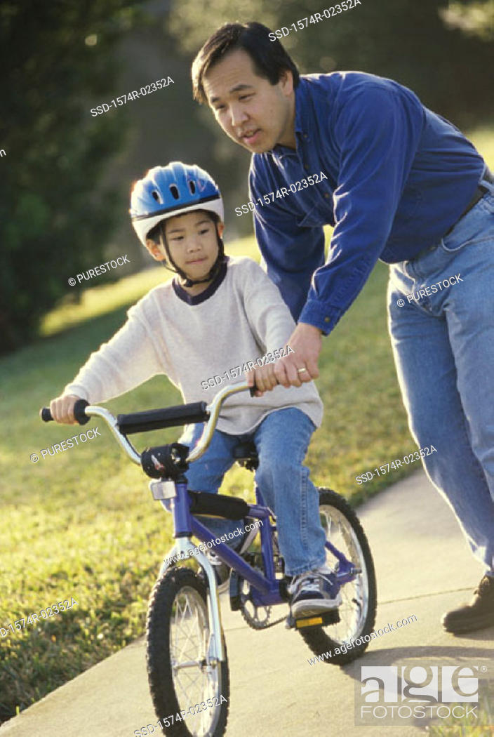 Stock Photo: Father helping his son ride a bicycle.