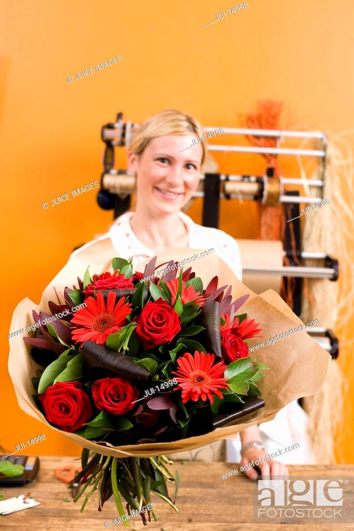 Stock Photo: Female florist with bouquet of flowers, smiling, portrait.