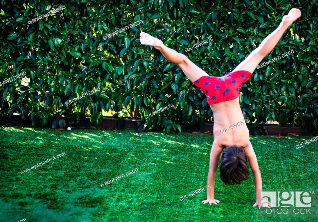 Stock Photo: Boy doing handstand on grass.