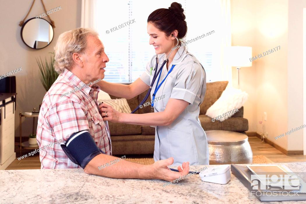 Stock Photo: Caucasian nurse listening to chest of man with stethoscope.