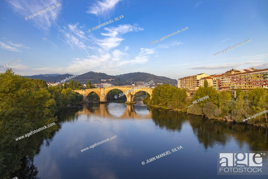 Stock Photo: Roman bridge in Ourense (Galicia, Spain), over river Miño and city scape in the background.