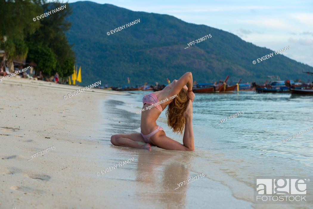 Stock Photo: Girl practicing yoga in pigeon pose on the beach with Thai longtail boats, Ko Lipe island.