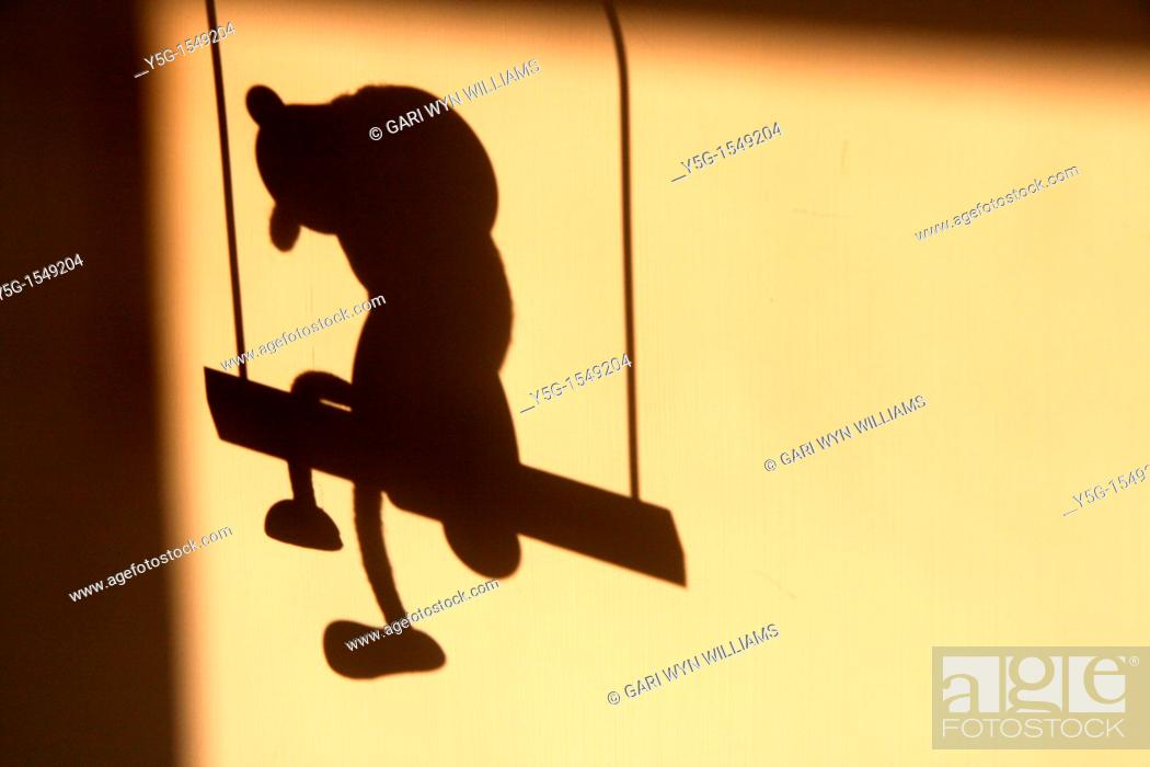 Stock Photo: shadow of toy dog sitting on a swing on wall.