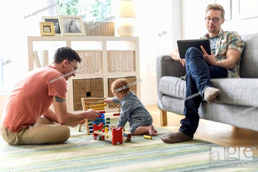 Stock Photo: Caucasian gay fathers and baby relaxing in living room.
