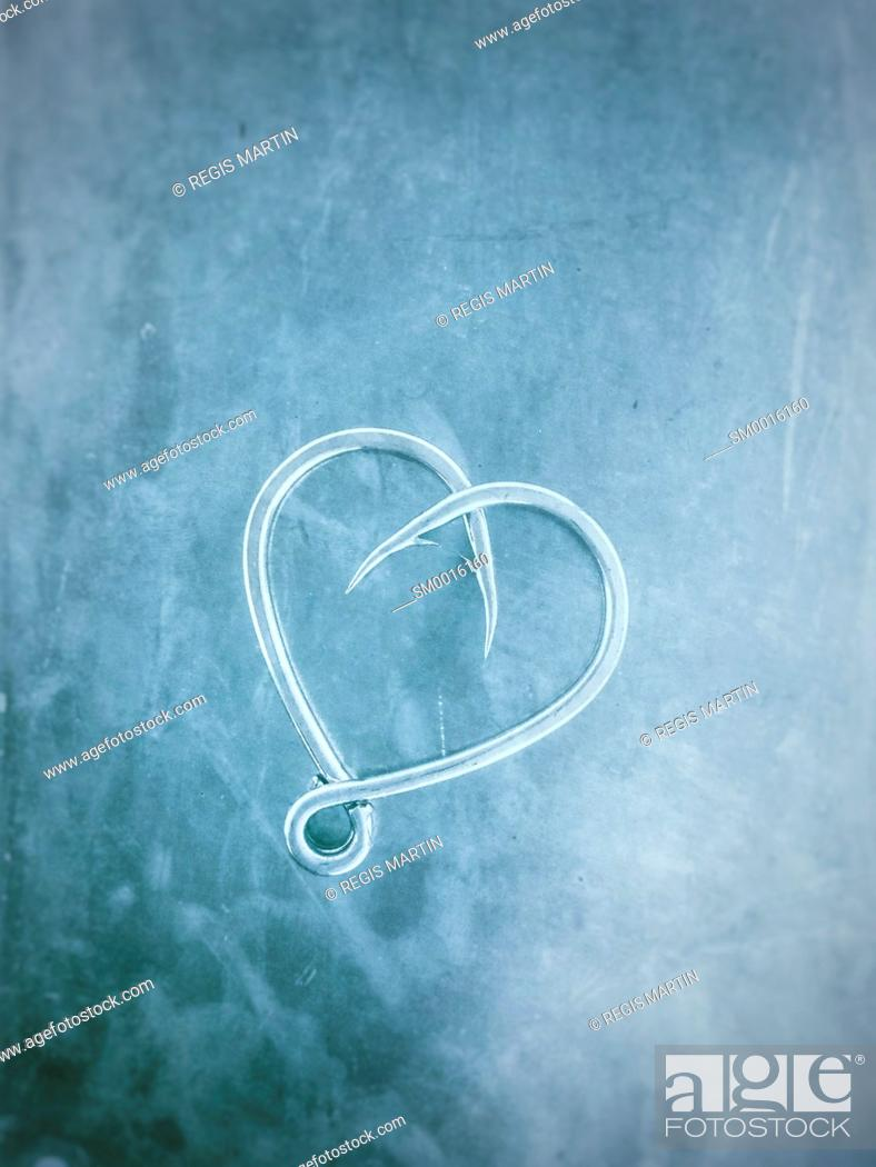 Stock Photo: Two fishing hooks placed to look like a love heart.