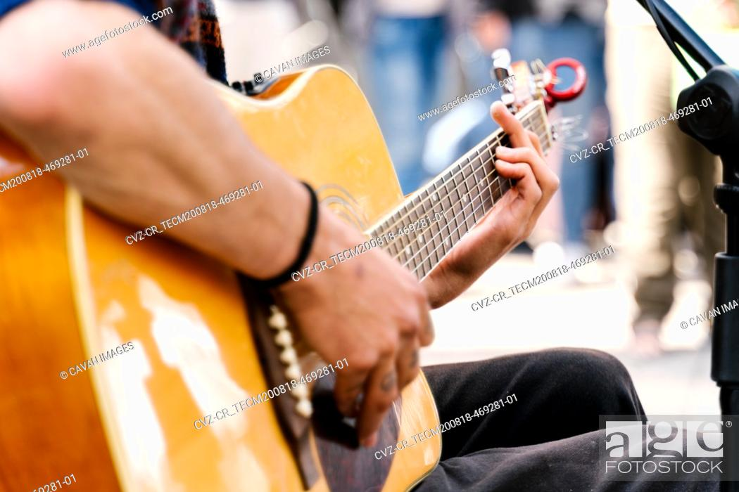 Imagen: Selective focus on the hands of a young man playing a guitar in a crowded street.