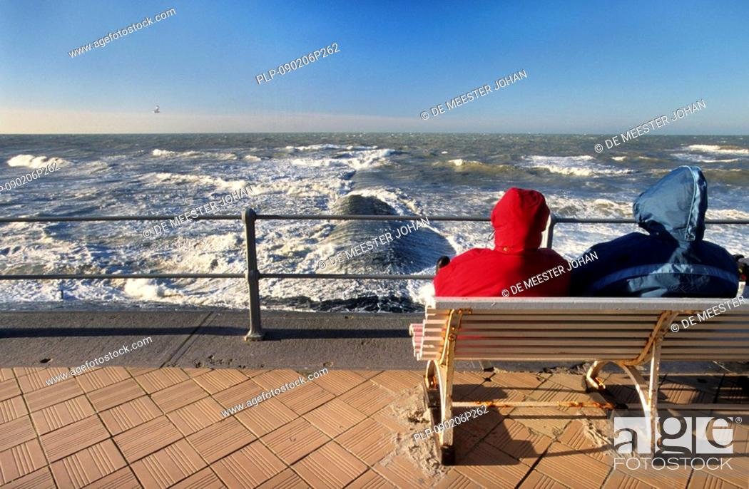 Stock Photo: Tourists on bench on sea dyke looking at the waves and breakwater in winter, Ostend, Belgium.
