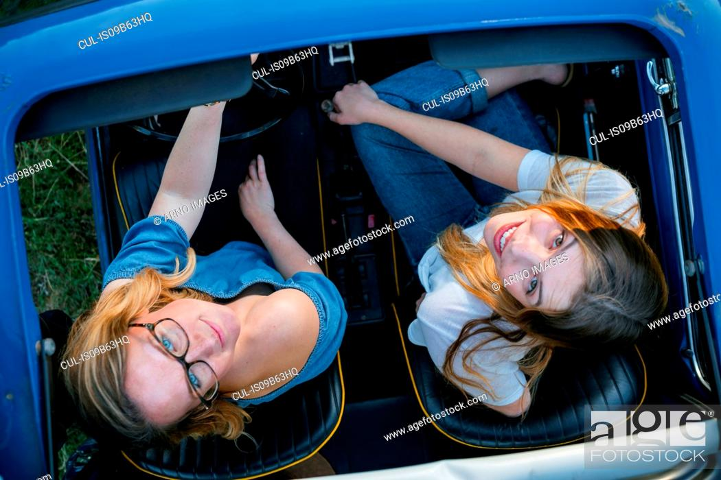 Stock Photo: Overhead view of friends in convertible car looking up, Firenze, Toscana, Italy, Europe.