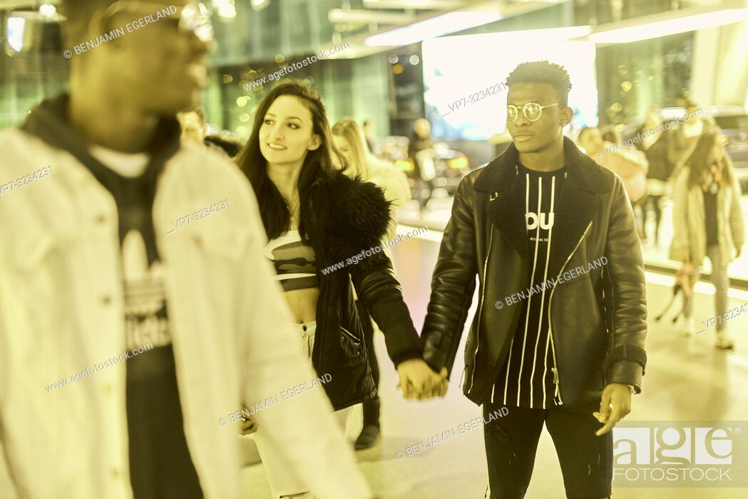 Stock Photo: couple walking together in shopping mall, happy enjoying togetherness, in Munich, Germany.