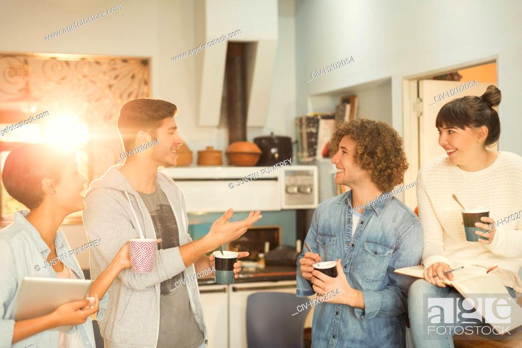 Stock Photo: Young adults hanging out talking drinking coffee.