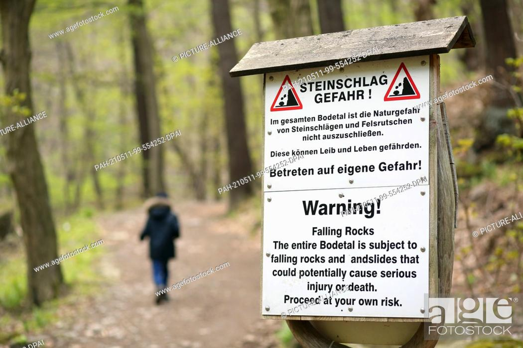 """Stock Photo: 07 May 2021, Saxony-Anhalt, Thale: A warning sign with the inscription """"""""Rockfall danger!"""""""" in the Bode Valley. The spring-like weather is again attracting many."""