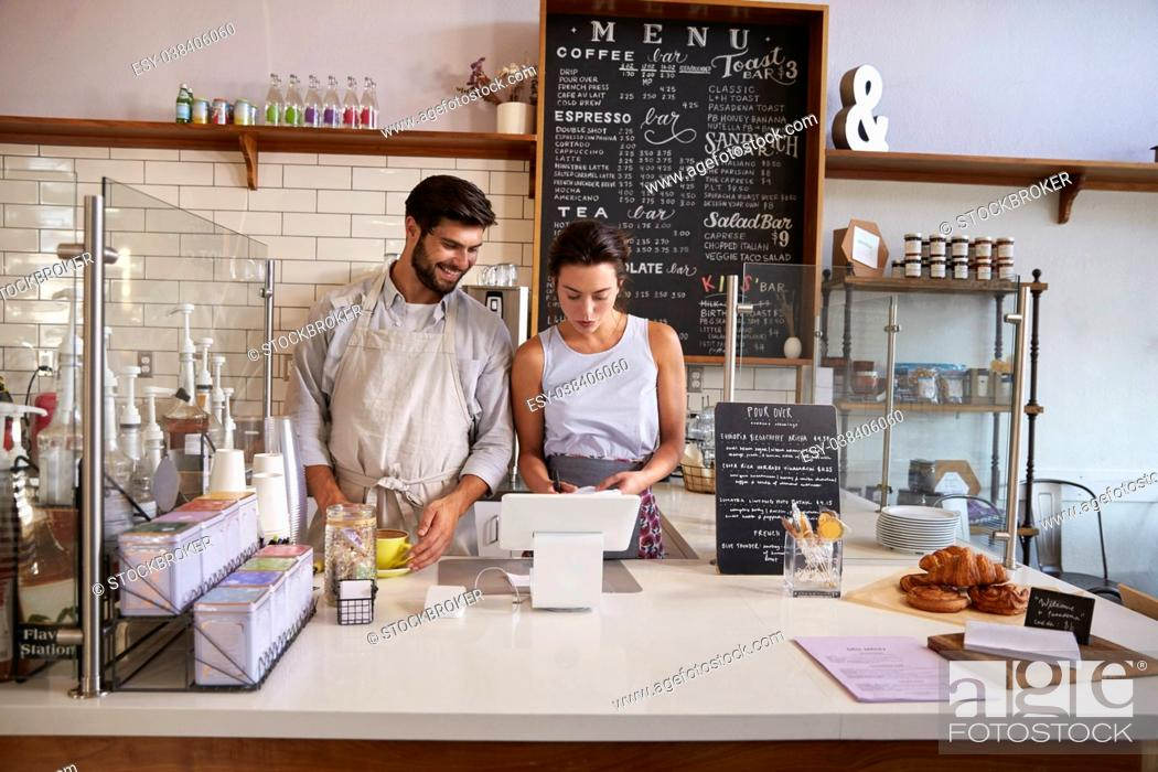 Stock Photo: Couple working together at the till in a coffee shop.