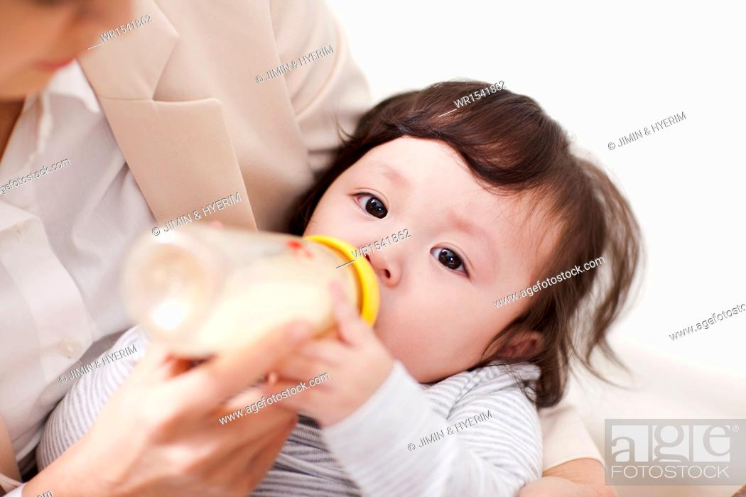 Stock Photo: a business woman feeding a baby.