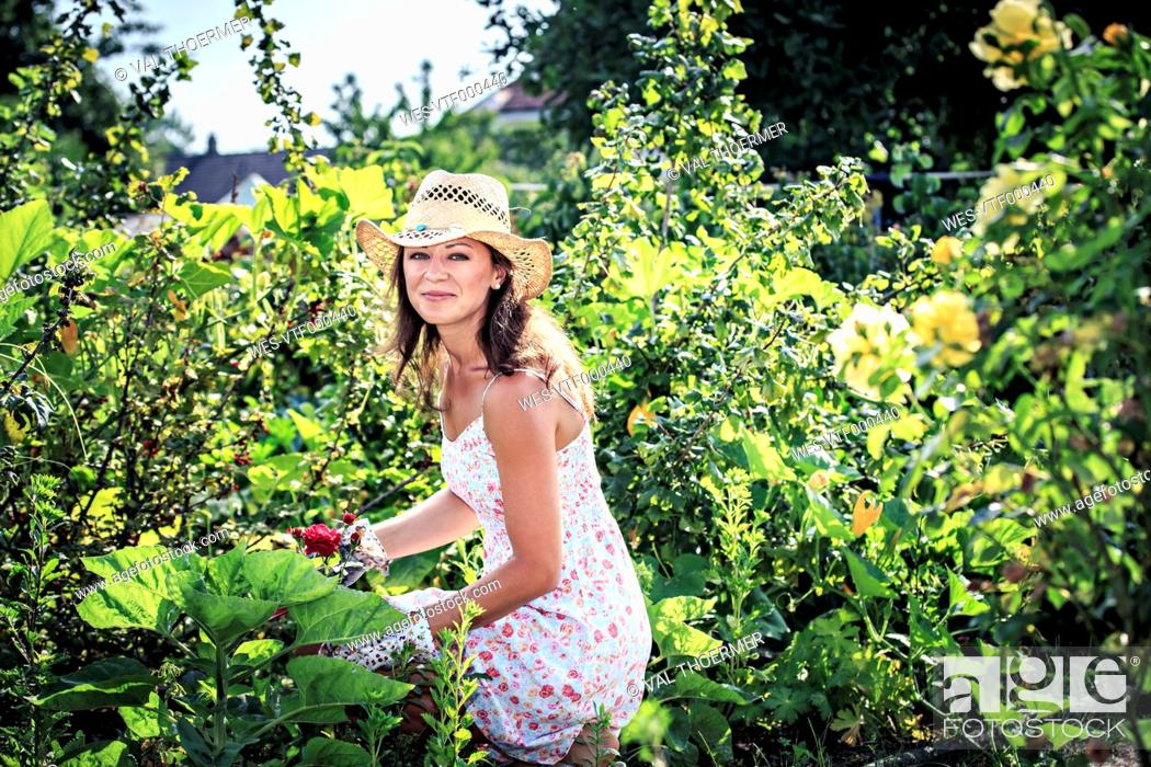 Stock Photo: Portrait of smiling woman working in the garden.