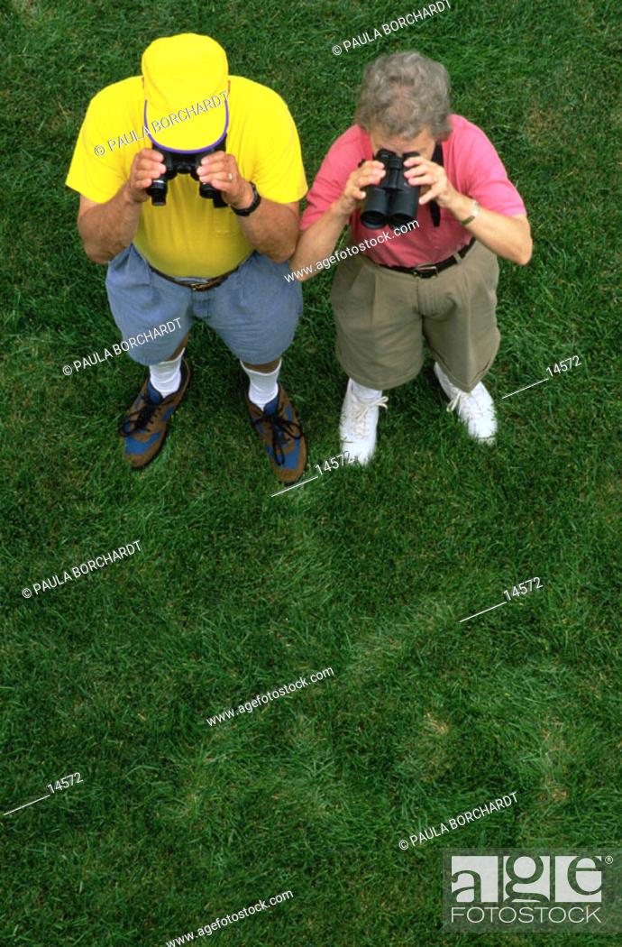 Stock Photo: Two seniors looking through binoculars.