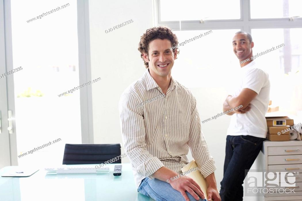 Stock Photo: Two businessmen in an office smiling.