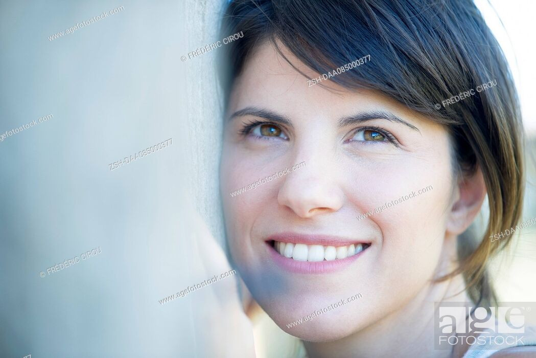 Imagen: Woman resting head on tree trunk, smiling cheerfully.