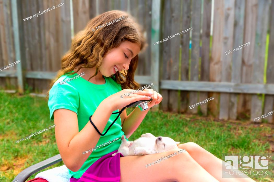 Stock Photo: Kid girl taking photos to puppy dog pet with camera in outdoor backyard.