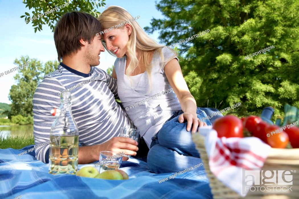 Stock Photo: Germany, Cologne, Young couple in meadow, smiling.