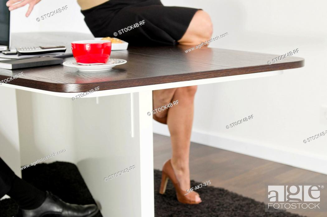 Stock Photo: Woman sitting on desk with cup of coffee.