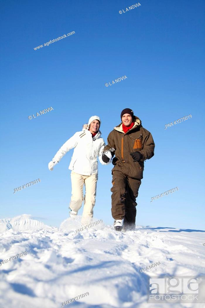 Stock Photo: Young couple holding hands, running in snow.